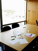 Papers and pens on table in empty meeting room