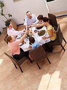 Multi generational family toasting glasses at dining table, smiling
