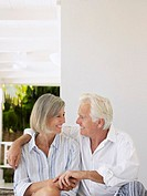 Senior couple sitting on verandah looking in eyes and smiling