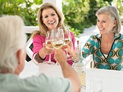Three people toasting with wine glasses sitting at verandah table (thumbnail)