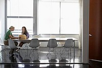 Two office workers sitting in conference room