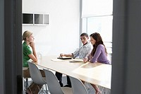 Three office workers sitting in conference room