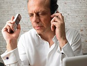 Mature businessman using two mobile phones, eyes closed