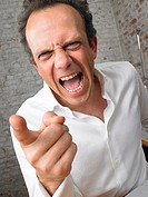 Businessman pointing and shouting at camera ,