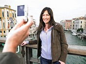 Close up of man´s hand taking photograph of woman Grand Canal, Venice, Italy