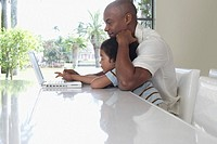 Father and son 5_6 years using laptop in dining room side view