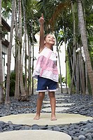 Girl 5_6 years standing on stepping stone on path pointing up