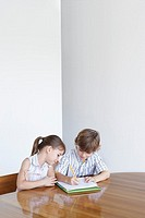 Boy 7-9 and girl 5-6 doing homework together (thumbnail)