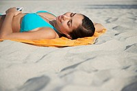 Teenage girl 16_17 using mp3 player lying on beach