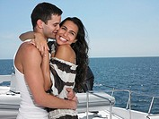 Young couple embracing on yacht man kissing woman