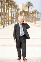 Senior businessman using mobile phone walking on promenade