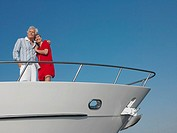 Middle_aged couple standing in bow of yacht