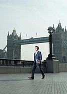 Young business man walking in front of Tower Bridge (thumbnail)