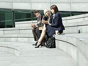 Three business people sitting on stairs outdoors talking side view
