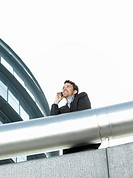 Businessman standing behind pipe outside office building using mobile phone low angle view (thumbnail)