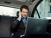 Mid adult businessman sitting at back seat of car using laptop and mobile phone (thumbnail)