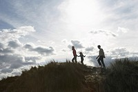 Silhouette of parents and daughter 5-6 walking on sand dunes (thumbnail)