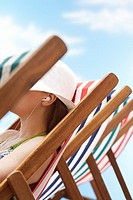 Woman wearing earphones sitting in deckchair side view