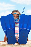 Girl 7_9 years sitting in flippers and snorkling mask on beach