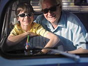 Boy 8-10 and grandfather in sunglasses sitting in backseat of car, portrait