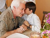Boy 8-10 whispering in grandfather´s ear at dining table