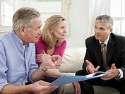 Senior couple sitting on sofa with financial advisor
