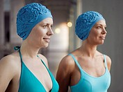 Two women wearing swimming caps and bathing suits