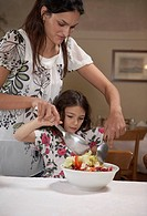 Woman helping daughter 5-7 to toss salad