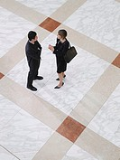 Business man and business woman talking elevated view