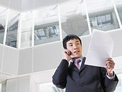 Business man using mobile phone in atrium of office building low angle view