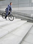 Business man riding bicycle down steps side view
