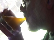 Photo of a silhoutted man drinking an alcoholic beverage