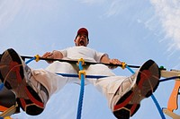 Latino man holding onto playground ropes