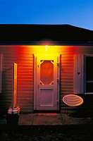 Illuminated roadside motel room entrance door and porch with chair at dawn