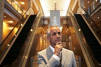 Businessman standing by escalators