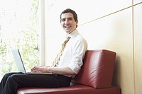 Friendly businessman on sofa with laptop
