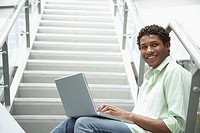 Young man sitting on stairway with laptop