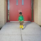Preschool boy with backpack trudging toward school door