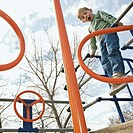 Little boy playing on monkey bars