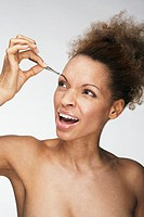 Woman grimacing as she plucks her eyebrows