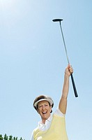 Excited golfer holding up her putter