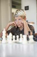 Boy sitting behind a chess game