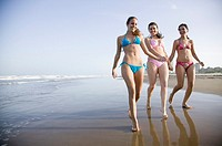 Young women walking along beach (thumbnail)