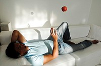 Young man lying on couch and tossing an apple in the air