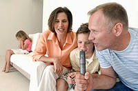 Close-up of a mid adult couple with their son singing into a microphone and their daughter sitting in the background