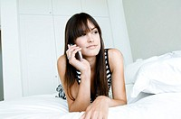 Mid adult woman lying on the bed and talking on a mobile phone