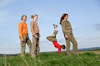 Family in field with boy doing handstand