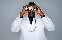 Close-up of a businessman looking through a pair of binoculars
