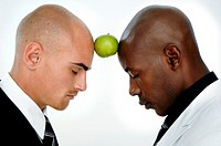 Close-up of two businessmen balancing an apple on foreheads