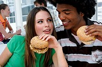 Close-up of a teenage couple holding burgers and looking at each other
